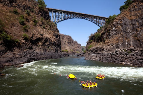 Adventure travel, people white water rafting on the Zambezi River at the Victoria Falls Bridge, Zambia, Africa