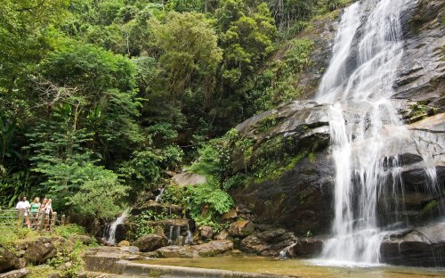 Tourists enjoy a waterfall and scenery of the Tijuca National Park in Rio with a slow shutter speed to blur the water.. Image shot 02/2007. Exact date unknown.